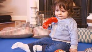 Cute baby girl playing with toy telephone