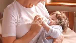 Mother feeding milk to her baby