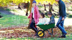 Parents carrying their son and daughter in a wheelbarrow