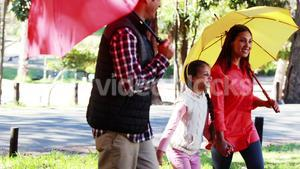 Family walking together in park with umbrella