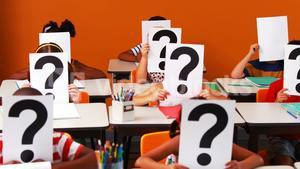 School kids covering their face with question mark sign