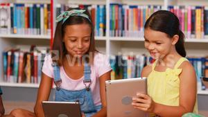School kids using digital tablet in library