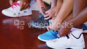 Girls tying shoe laces in basketball court