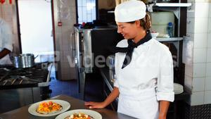 Smiling chef standing at kitchen counter