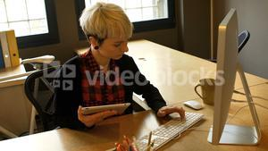 Female business executive using digital tablet and computer