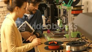 Male and female graphic designer interacting over a machine