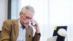 Businessman talking on mobile phone while working at desk