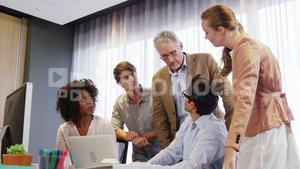 Businessman and coworkers discussing over laptop at desk