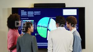 Businesspeople interacting over a pie chart