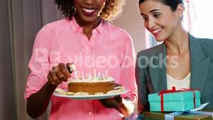 Businesswoman lighting candles on cake with colleague