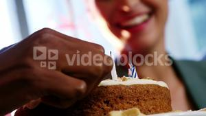 Hand of businesswoman lighting candles on cake with colleague