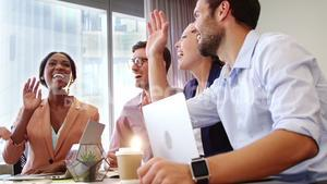 Businesspeople interacting and giving high five to each other