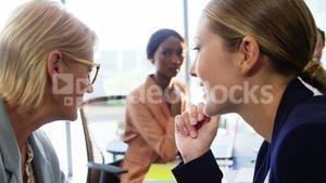 Two businesswomen whispering