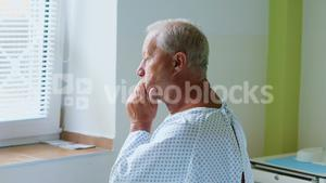 Thoughtful senior man sitting on a bed