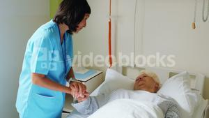 Nurse consoling senior patient with doctor