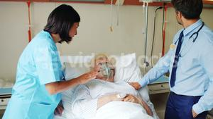 Female doctor putting oxygen mask on patient