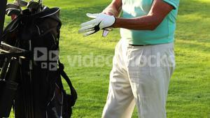 Mid section of male golfer wearing golf glove