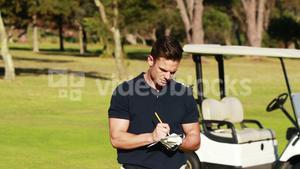 Golfer writing on paper