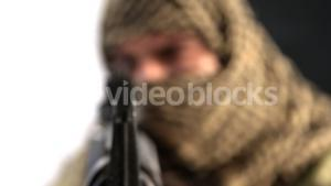 Soldier with covered face aiming rifle