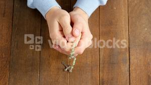 Praying hands holding rosary