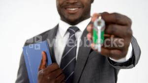 Portrait of businessman with documents holding up keys