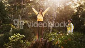 Excited female mountain biker with arms outstretched