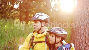 Mountain biking couple walking on forest trail with bike