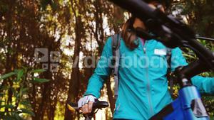 Female mountain biker walking with bike