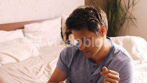 Man using mobile phone while wife sleeping on bed