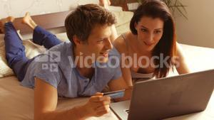 Couple shopping online on laptop using credit card