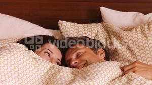 Couple relaxing on bed in the bedroom