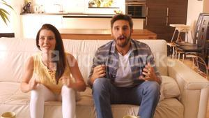 Excited couple relaxing on sofa and watching television