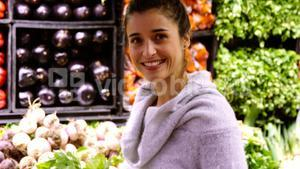 Smiling woman buying leafy vegetables in organic section