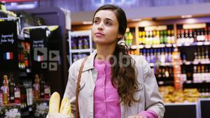 Woman walking with shopping cart in grocery section