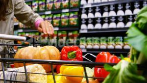 Woman putting grocery in shopping cart
