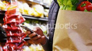 Man using mobile phone while holding grocery bag