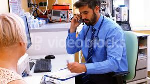 Doctor sitting at his desk and talking on phone