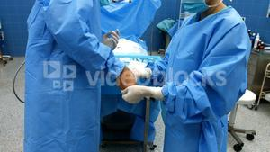 Nurse helping a surgeon in wearing surgical gloves