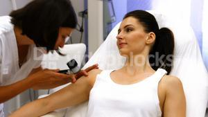 Doctor performing laser hair removal on patient skin