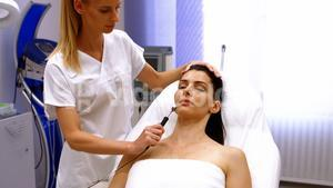 Doctor performing laser hair removal on patient