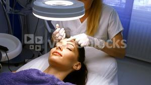 Doctor inserting facial injection on female patient forehead