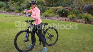 Female cyclist drinking water in park