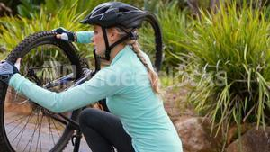 Female cyclist repairing bicycle tyre