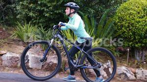 Female cyclist walking with mountain bike in forest