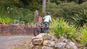 Female cyclist walking with mountain bike in forest at countryside