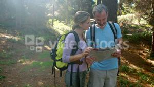 Hiker couple interacting while looking at map