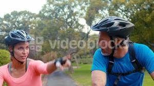 Couple interacting face to face while riding bicycle