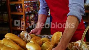 Male staff keeping a basket of bread on counter