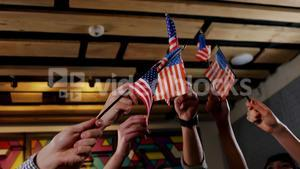 Group of friends waving american flag