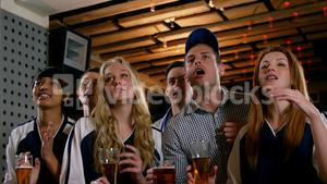 Group of friends watching tv in bar